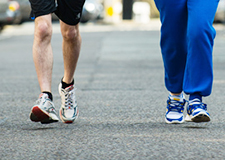 2 pairs of legs and feet jogging along tarmac