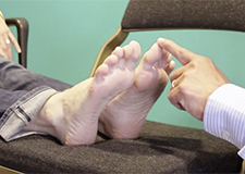 A healthcare professional touches the toe of a patient's feet, which are laid on a chair