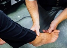 Medical expert conducts a foot check, holding the patient's foot by the ankle