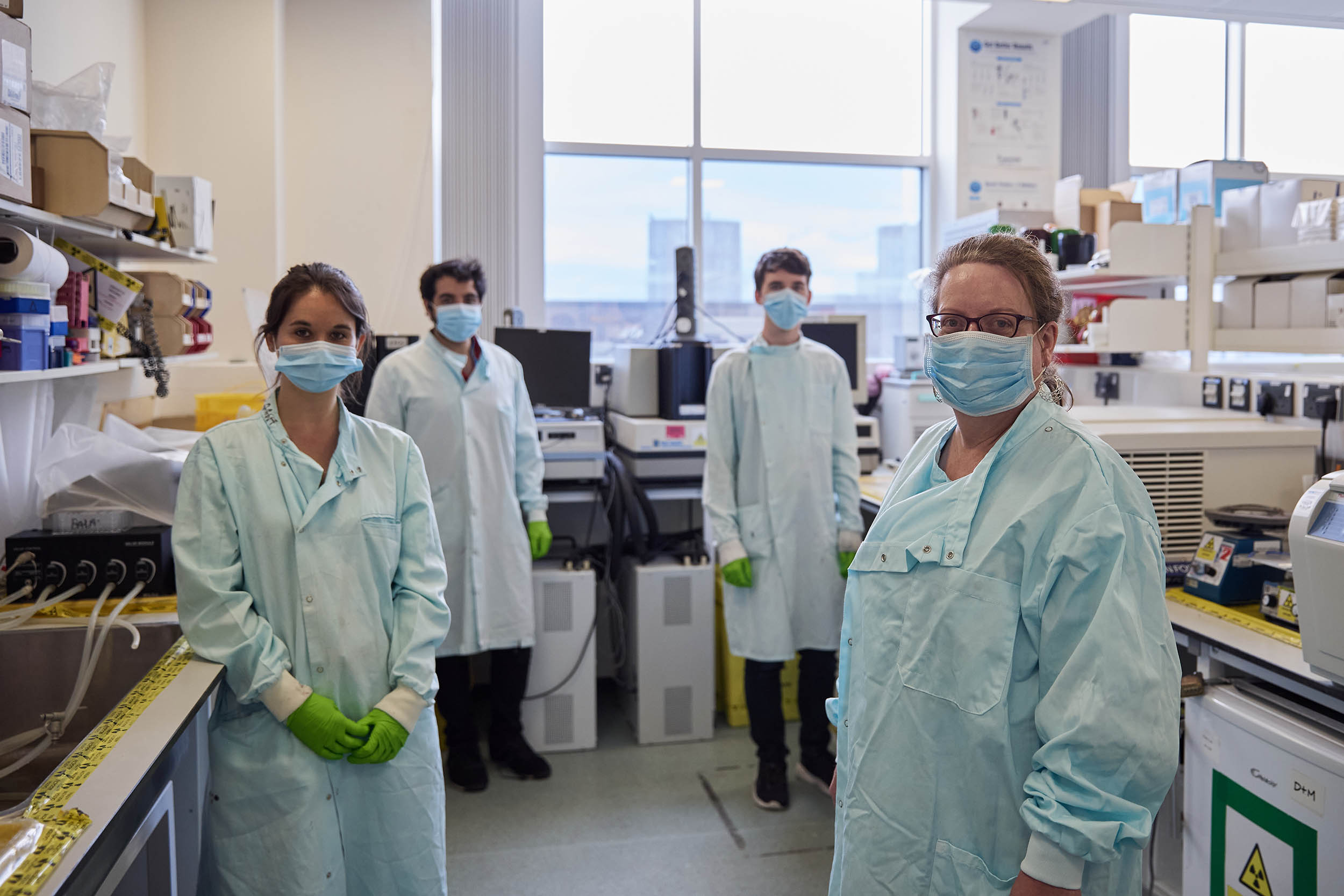 Our approach to research - researchers in the lab wearing masks