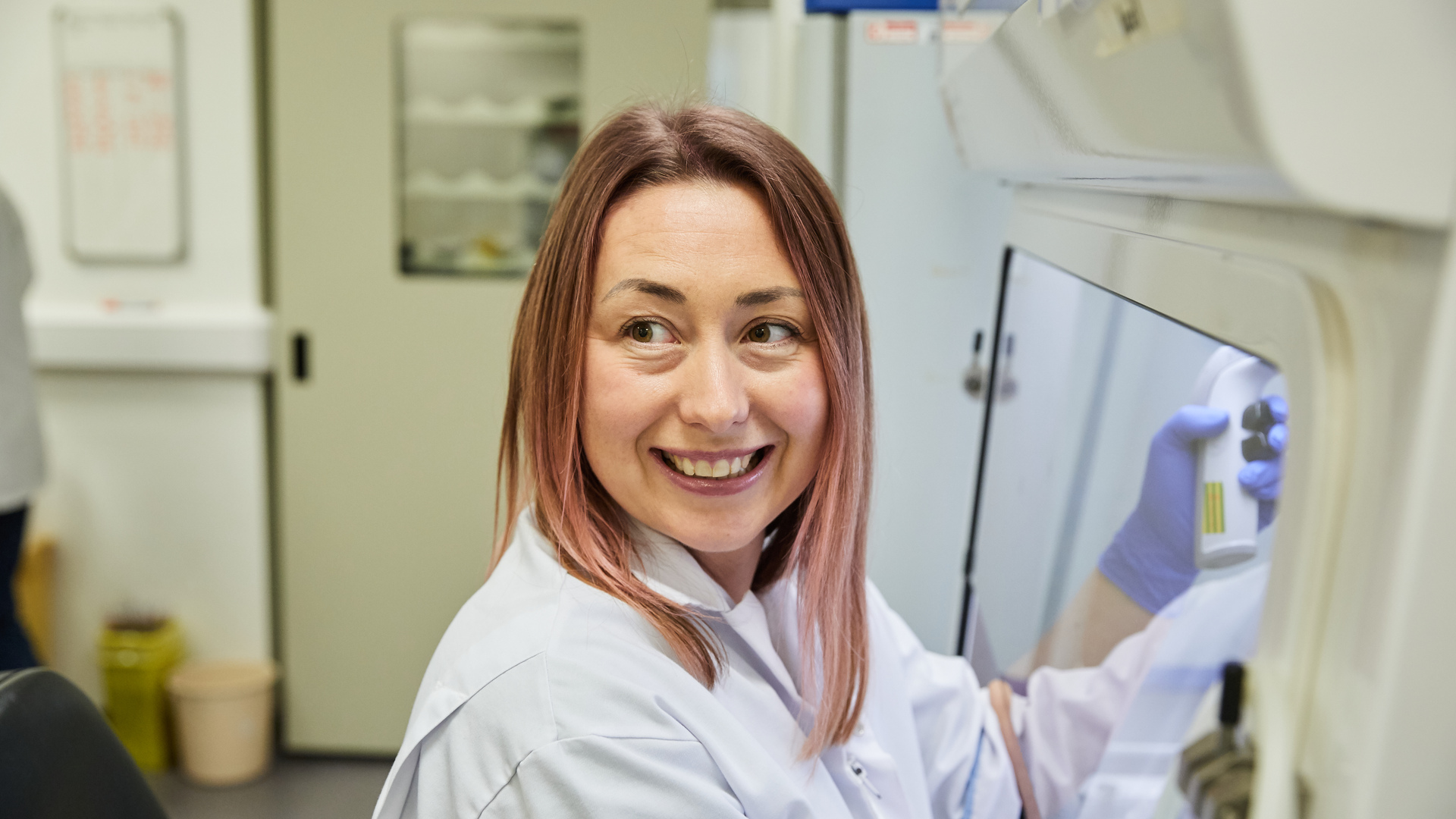 Our approach to diabetes research - a scientist smiling whilst working in a lab