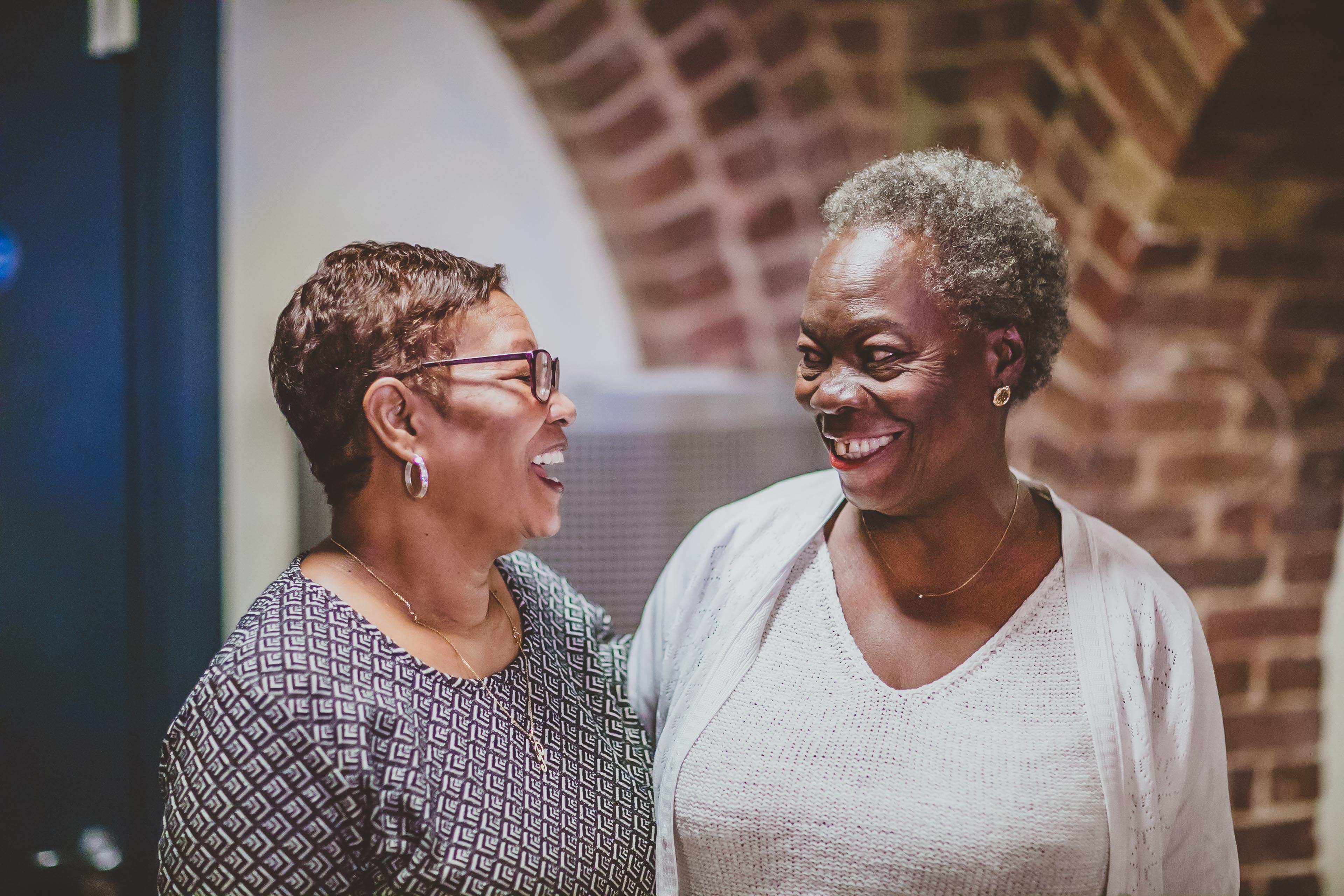 Two women look at each other, smiling