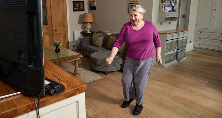 A lady moving as she joins in with a Diabetes UK Get Moving class