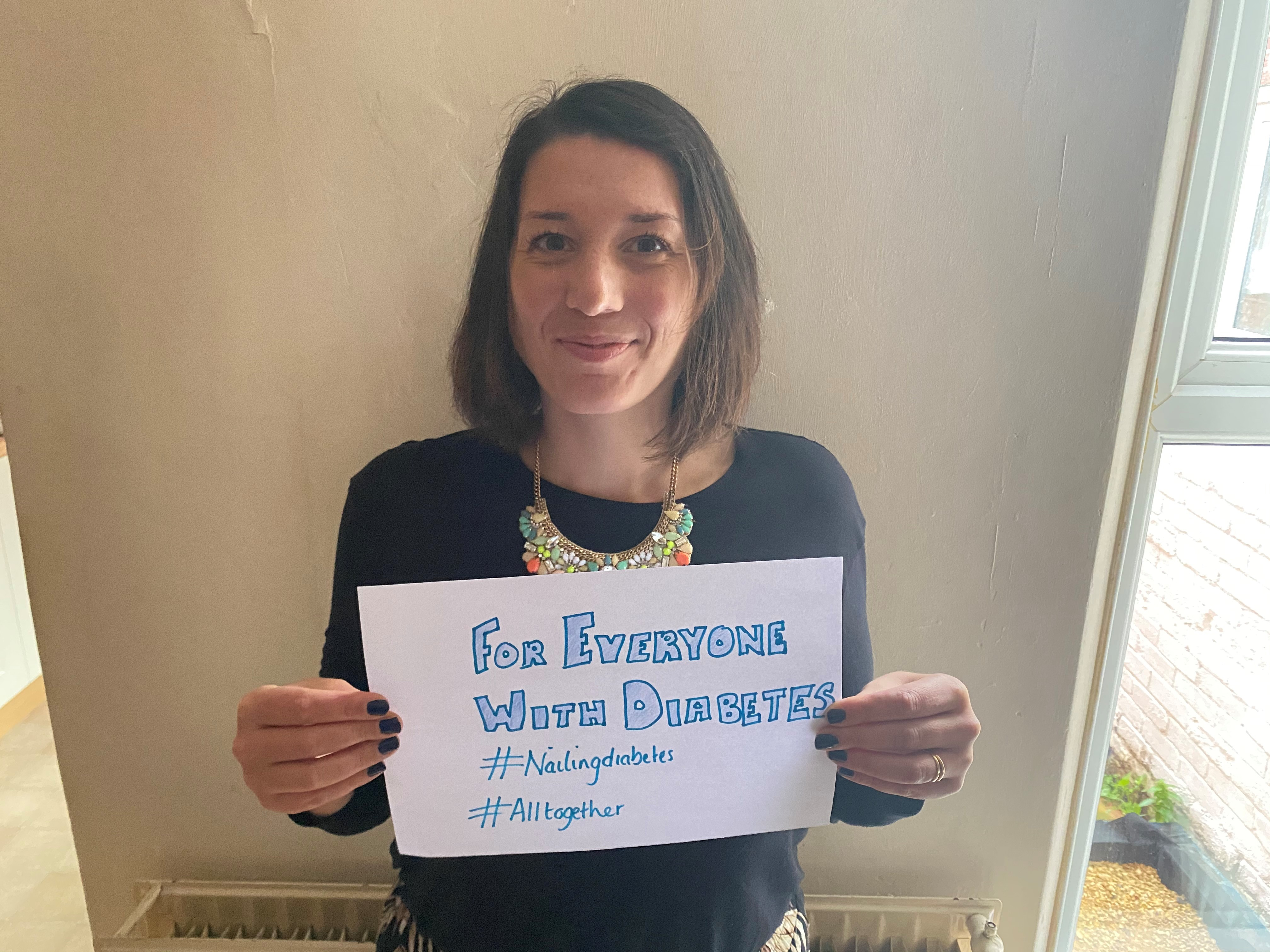 Regional Fundraiser Lauren Barker holding a sign which reads 'for everyone with diabetes'