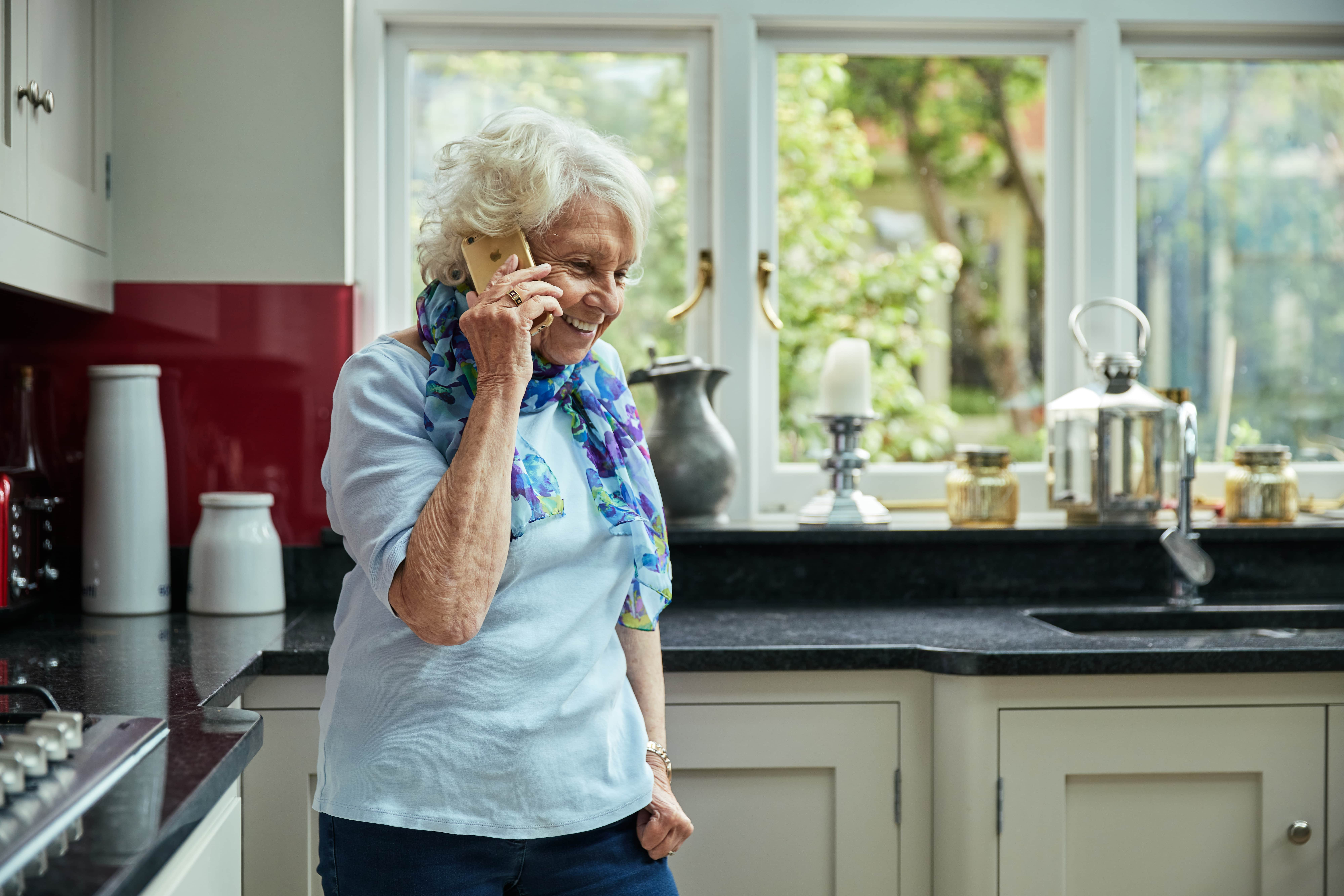 A lady smiling on the phone as she calls the Diabetes UK Helpline service
