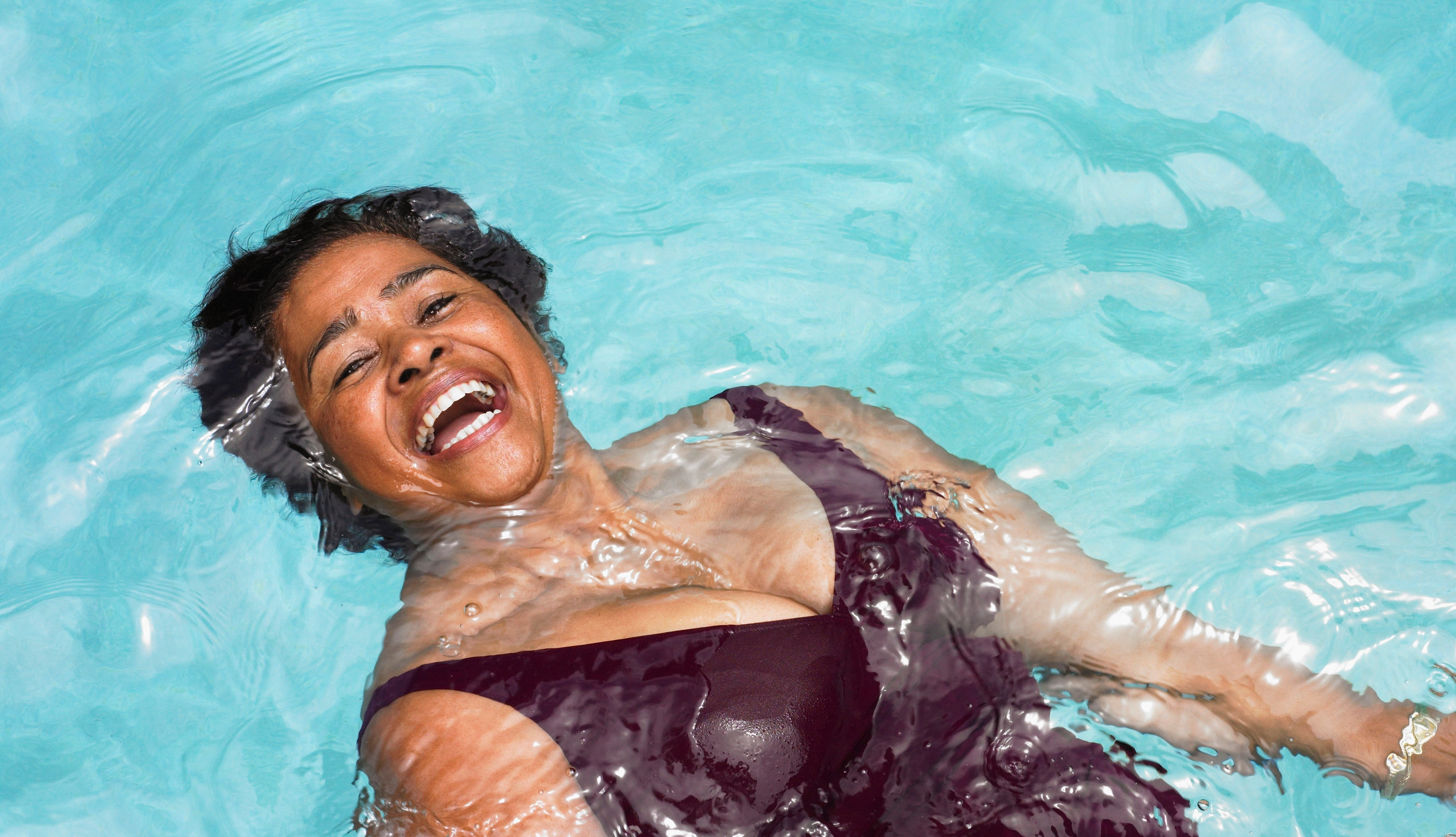 A lady smiling as she takes part in Swim22, Diabetes UK's swimming challenge