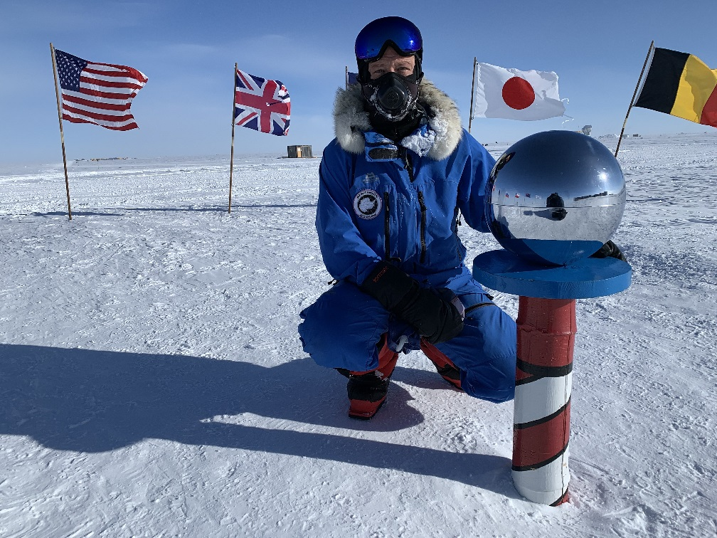 Neil Hunter kneels next to the pole, which has a spherical, mirrored top. international flags are placed in the show behind him