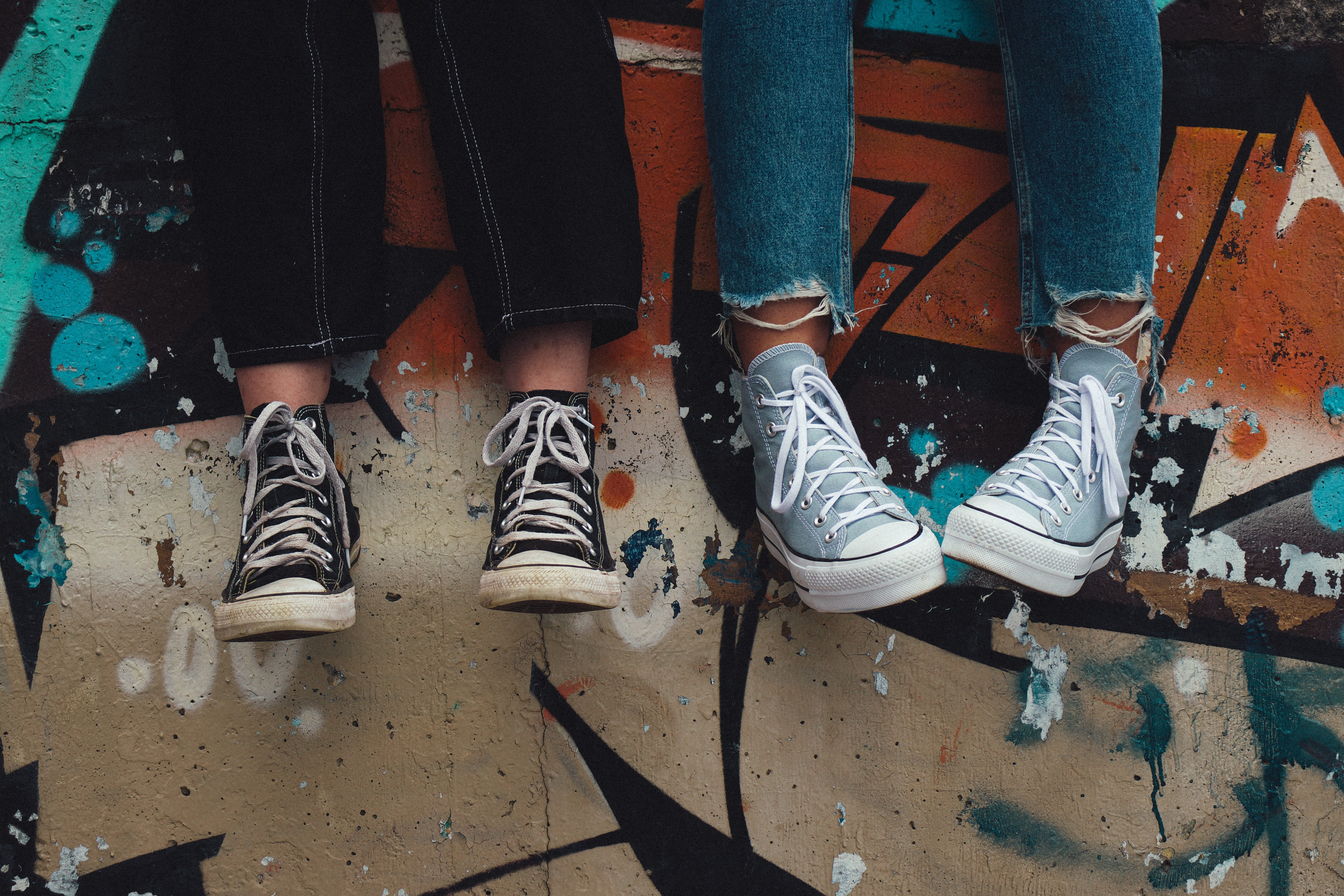 Some teenagers seem to sit on a wall wearing trainers, only their feet can be seen in front of some grafitti