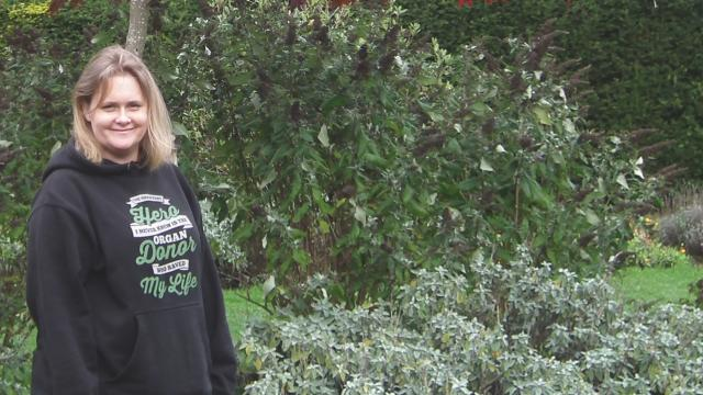 Amanda stands in a garden smiling