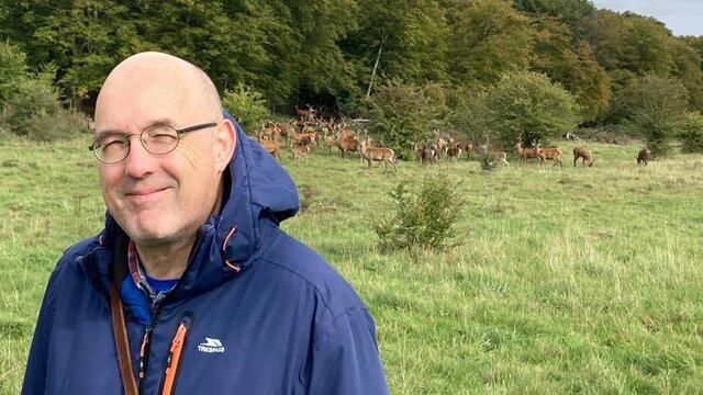 David smiling at the camera in front of some deer in a park