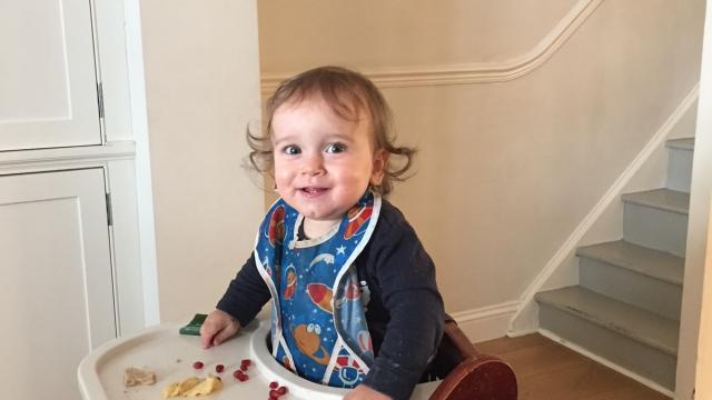 A young child in a high-chair eating food