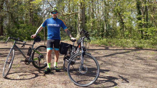 Brian wearing his Diabetes UK top and standing with his bike