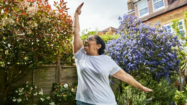 Riffat practicing a yoga pose in her garden as she gets moving at home
