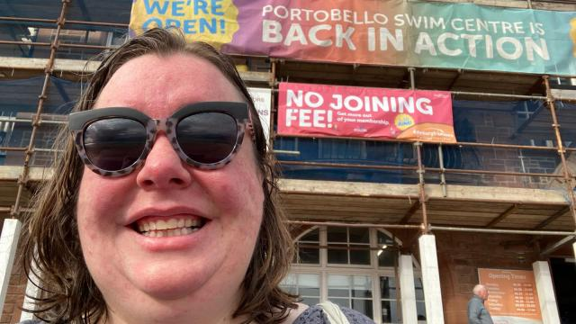 Ruth smiling as she stands outside her local swimming pool