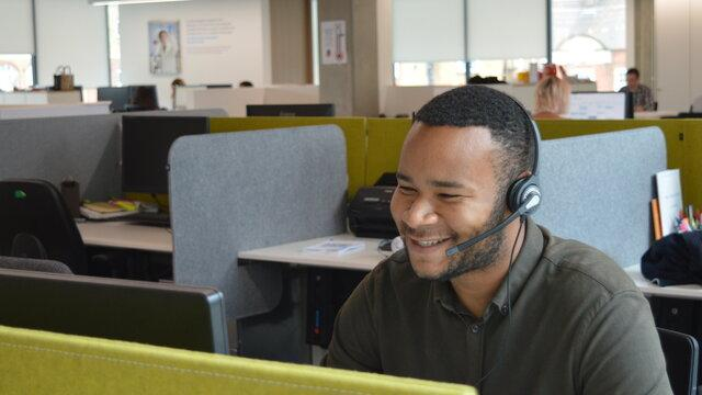 A Diabetes UK Helpline Advisor smiling as he chats to a supporter over the phone