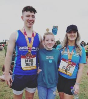Pic shows Daniel and Leanne smiling at the end of the race with their little sister Erin standing in between them. The three of them have their arms round each other.