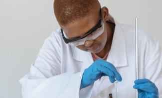 A scientist in a white lab cot, blue gloves and goggles looking at scientific equipment