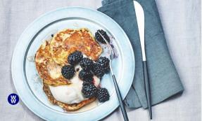 Pancakes with yoghurt and berries on a plate with a knife next to it