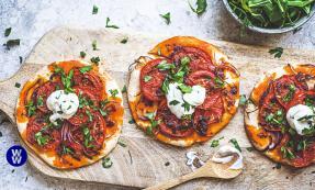 Three harissa tomato tarts on a wooden chopping board