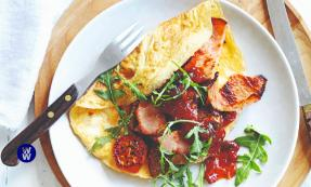 A sausage bacon omelette next to some salad on a plate