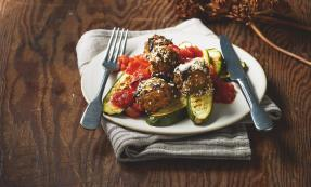 A plate of aubergine meatballs and tomato sauce with courgettes