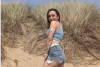 Natalie stands on a beach, with diabetes tech on her arm and leg