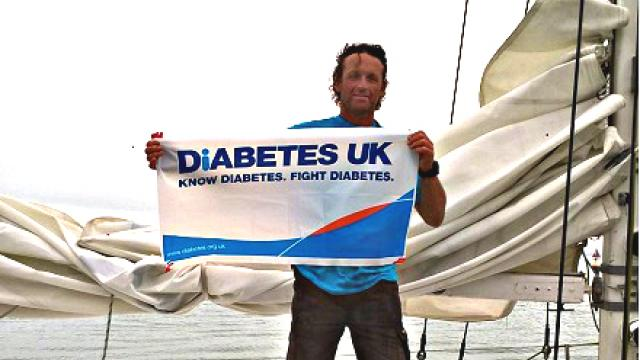 Adam smiling with a Diabetes UK poster