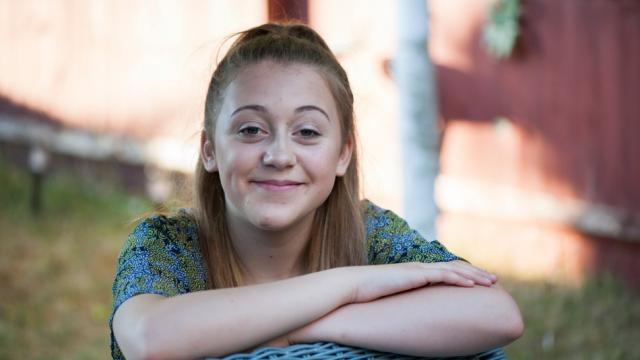 Girl smiling to camera with arms crossed