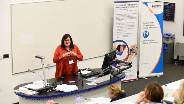 A photo of a woman at the front of a lecture hall next to a Diabetes UK banner