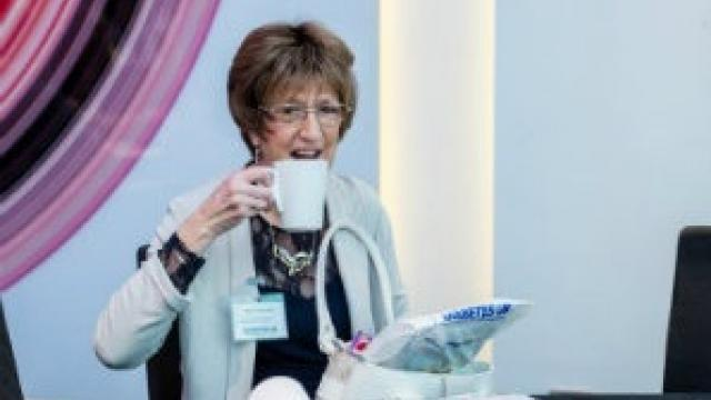 Lady drinking a cup of tea at a DUK event