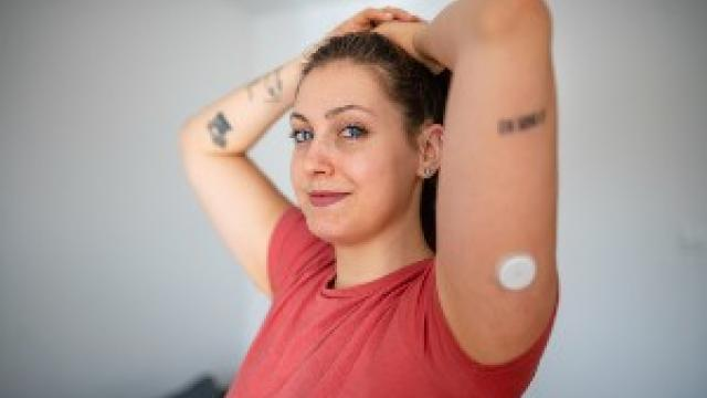 A woman in a red top with her arms above her head, showing a continuous glucose monitor on her arm