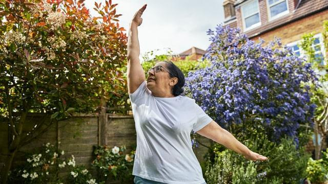 A lady with diabetes doing some yoga in her garden