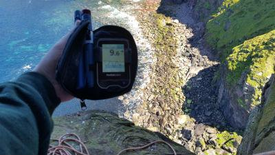 Steve holding his flash glucose monitor as he climbs the Old Man of Hoy