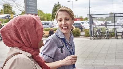 HCP walking outside alongside a patient talking